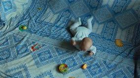 Infante che si trova sul letto, giocante con i giocattoli nel timelapse archivi video