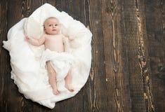 Infante coberto com a cobertura branca Bebê que encontra-se na edredão macia imagens de stock