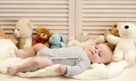 Infante com olhos azuis e sorriso calmo entre ursos de peluche foto de stock