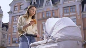 Infante d'oscillazione della mamma occupata nervosa in carrozzina e panino di masticazione, mangiando spuntino in parco stock footage