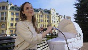 Infante d'oscillazione femminile attraente felice in carrozzina che gode del fine settimana della molla in città archivi video