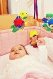 Infante na cama com brinquedos Fotografia de Stock Royalty Free