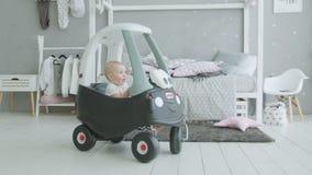 Infante sveglio che gioca in automobile di bambino in imterior domestico stock footage