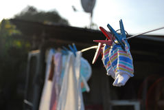 Infantile mittens drying on the string. The photography of the couple of infantile mittens, which are drying on the string. The mittens are pinned with Stock Photography