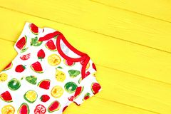 Infants dainty design summer clothes. Baby-girl soft printed t-shirt on yellow background, top view stock images