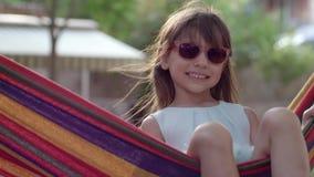 Infanzia felice, bambina allegra negli occhiali da sole che oscillano in amaca e primo piano sorridente sulla natura stock footage