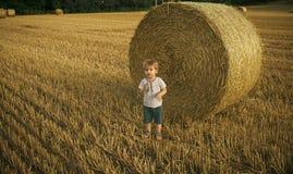 Infanzia felice Ragazzo adorabile del bambino divertendosi con le balle di fieno fotografie stock
