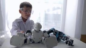 Infanzia moderna, giocattolo curioso del robot del montaggio del bambino con intelligenza artificiale in laboratorio stock footage