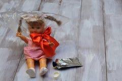 Infanzia persa Droghe e bambini Bambola con il sacchetto di plastica, arco rosso del raso, tubo della colla su fondo di legno leg fotografia stock