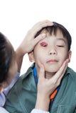 Infección en un muchacho, ojo ascendente de Pinkeye (conjuntivitis) del control del doctor foto de archivo