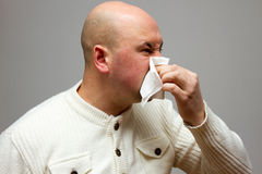 Infected man blowing his nose in tissue paper because of being ill  on gray background. On gray background Royalty Free Stock Photography