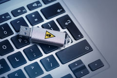 Infected memory drive is on notebook. Security threat concept. Close up top view of USB flash stick infected dangerous virus is on keyboard of laptop Royalty Free Stock Image
