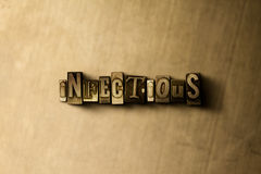 INFECTIEUX - le plan rapproché du vintage sale a composé le mot sur le contexte en métal photographie stock