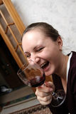 Infectious laughter. The laughing girl with red wine at home Royalty Free Stock Photo