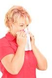 Infekująca dojrzała kobieta dmucha jej nos w tkance przez bein Fotografia Stock
