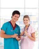 Infermiera e medico dei giovani che sorridono alla macchina fotografica Fotografie Stock