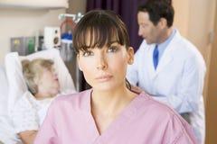 Infermiera ed il dottore che si levano in piedi nella stanza di ospedale Immagini Stock Libere da Diritti