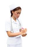 Infermiera femminile asiatica che scrive rapporto medico Fotografia Stock