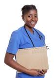 Infermiere africano di risata con l'archivio di un paziente Immagine Stock