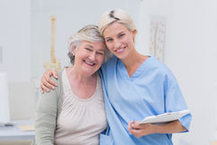 Infermiere amichevole con il braccio intorno al paziente senior in clinica Immagine Stock