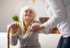 Infermiere che aiuta donna anziana a alzarsi Fotografie Stock Libere da Diritti