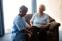 Infermiere che aiuta donna senior nell'allungamento delle gambe Fotografia Stock Libera da Diritti
