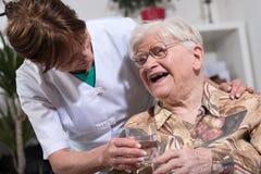 Infermiere che dà bicchiere d'acqua alla donna anziana Immagine Stock Libera da Diritti