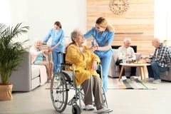 Infermiere che dà bicchiere d'acqua alla donna anziana in sedia a rotelle Assistenza della gente senior immagine stock