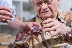 Infermiere che dà farmaco ad una donna senior fotografie stock