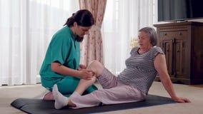 Infermiere che dà massaggio della gamba alla donna senior in una casa di riposo archivi video