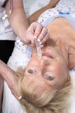 Infermiere che dà le gocce di naso al paziente Fotografie Stock Libere da Diritti