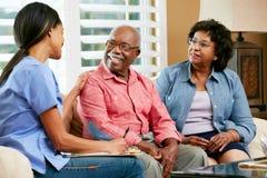 Infermiere che fa le note durante la visita domestica con le coppie senior Immagini Stock Libere da Diritti