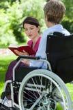 Infermiere che legge un libro con la donna più anziana Fotografia Stock
