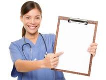 Infermiere che mostra lo spazio medico della copia della lavagna per appunti del segno Immagini Stock Libere da Diritti