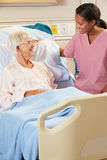 Infermiere che parla con paziente femminile senior nel letto di ospedale Immagini Stock