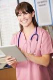 Infermiere che per mezzo della compressa di Digital alla stazione degli infermieri fotografia stock libera da diritti