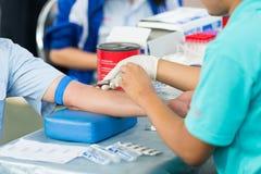 Infermiere che raccoglie un sangue da un paziente Fotografie Stock Libere da Diritti