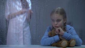 Infermiere che rende iniezione ad abbracciare malato della bambina teddybear dietro la finestra piovosa archivi video