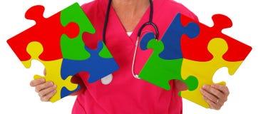 Infermiere che tiene due pezzi di puzzle che rappresentano consapevolezza di autismo Fotografie Stock Libere da Diritti