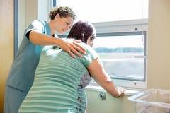 Infermiere Comforting Tensed Pregnant alla finestra dentro immagini stock
