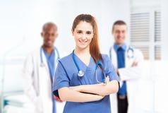 Infermiere davanti al suo gruppo di medici Fotografie Stock Libere da Diritti