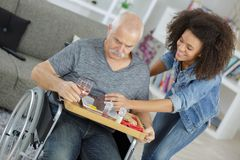 Infermiere della Comunità con l'uomo disabile anziano sulla sedia a rotelle immagini stock