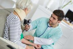 Infermiere di visita domestico che prende la pressione sanguigna della donna anziana fotografie stock libere da diritti