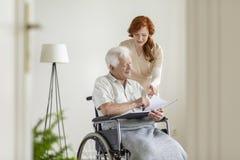 Infermiere e paziente in una sedia a rotelle che esamina insieme album di foto e sorridere immagini stock