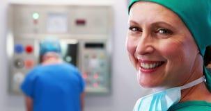 Infermiere femminile in cappuccio chirurgico al teatro di operazione video d archivio