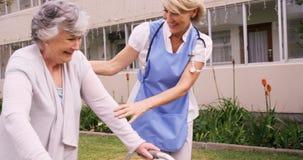 Infermiere femminile che assiste una donna senior per camminare video d archivio