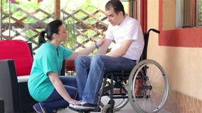 Infermiere femminile che consola uomo triste che si siede in sedia a rotelle stock footage