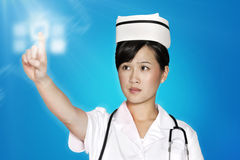 Infermiere femminile che per mezzo del touch screen futuristico sopra fondo blu Immagine Stock Libera da Diritti