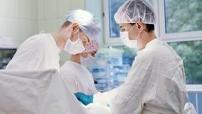 Infermiere femminile ed assistente maschio che lavorano con il chirurgo professionista che realizza operazione stock footage