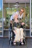 Infermiere gentile Talking alla donna anziana sulla sedia a rotelle immagini stock libere da diritti